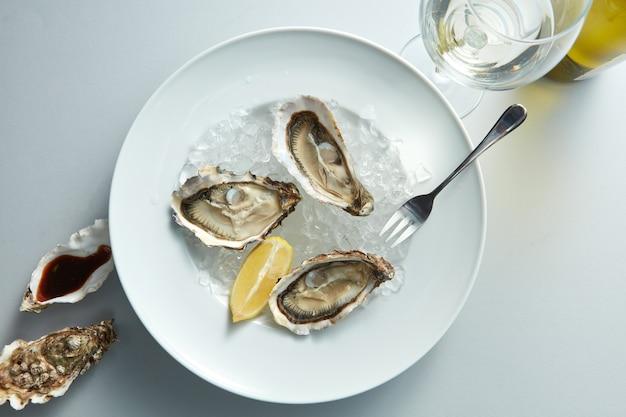 Owoce morza. pyszna ostryga z cytryną na białym talerzu i kieliszek wina w białym stole