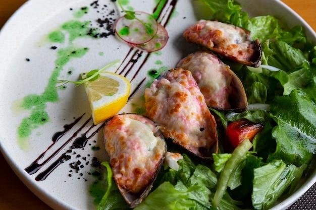 Owoce morza zapiekane w sosie śmietanowym i ser z małży z warzywami na białym talerzu w restauracji rybnej