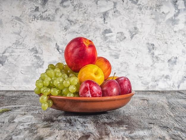 Owoce na glinianym talerzu nektarynki z zielonych winogron i czerwone śliwki letnie wino na lunch