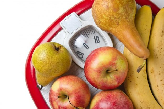 Owoce na podłodze wagi na białym tle