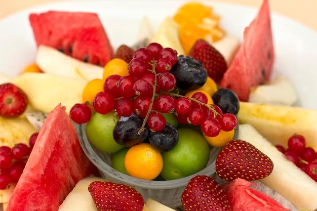 Owoce na talerzu. zielona śliwka, czerwona porzeczka, jagoda, truskawka, pęcherzyca, pitahaya