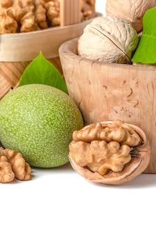 Owoce orzecha włoskiego różnych odmian leżą w drewnianych spodkach i koszyczkach na białym, izolowanym ba...