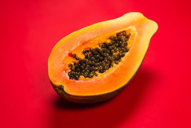 Owoce papai na pomarańczowym tle. owoc tropikalny. połowa papai.