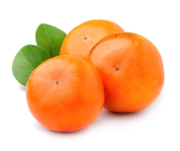 Owoce persimmon z liśćmi na białym tle.