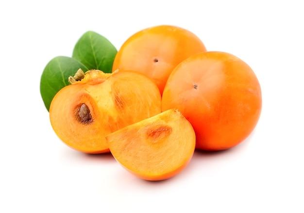Owoce persymony z liśćmi na białym tle