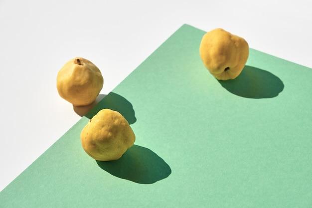 Owoce pigwy japońskiej na białym i miętowo zielonym papierze