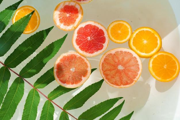 Owoce pomarańczy, cytryny, grejpfruta w wodzie z zielonymi liśćmi