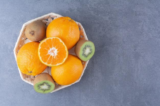 Owoce pomarańczy i kiwi w koszu na marmurowym stole.