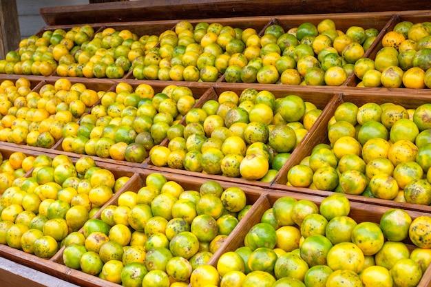 Owoce pomarańczy zabrudzone organicznie ułożone na drewnianej skrzyni w wiejskim sklepie spożywczym