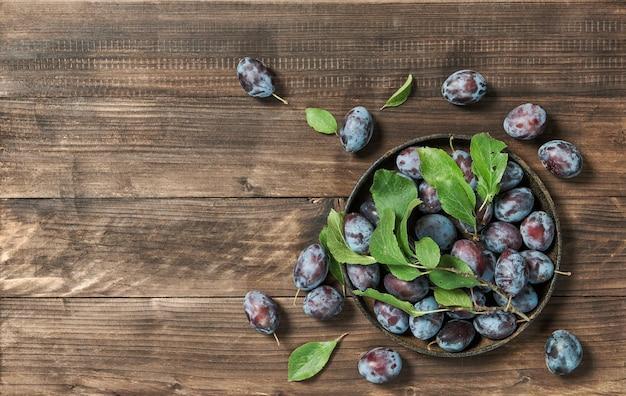 Owoce śliwki z zielonymi liśćmi na rustykalnym drewnianym tle