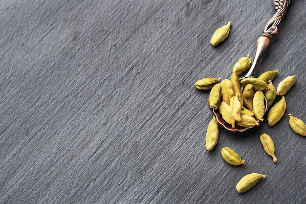 Owoce suchego całego kardamonu na czarnym betonowym stole. pikantna indyjska przyprawa.