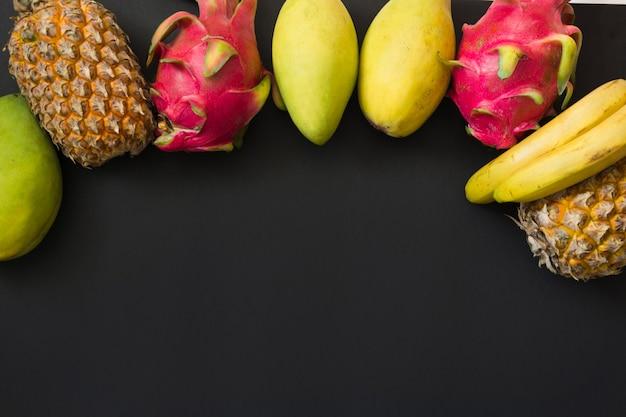 Owoce tropikalne ananas, banan, owoc smoka i mango na czarno. widok z góry.