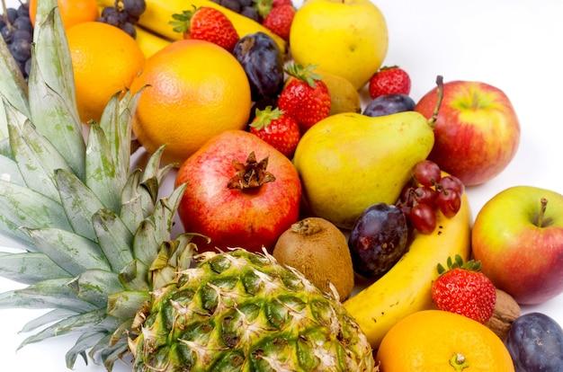 Owoce tropikalne. ananas. kokos, pomarańcza, banany i suche chipsy owocowe na różowym tle