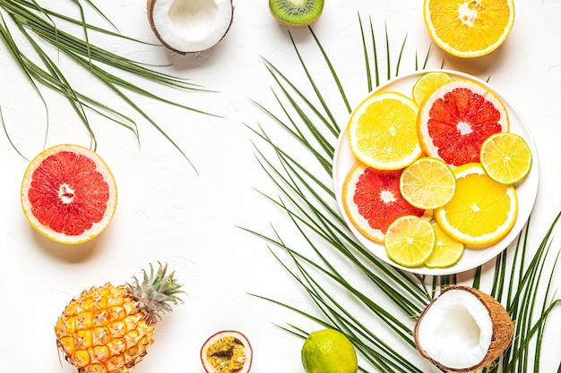 Owoce tropikalne i liście palmowe na białym tle, widok z góry.