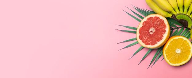 Owoce tropikalne lato transparent tło. banany, pomarańcze i grejpfruty na kolorowym różowym tle.