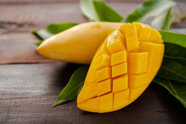 Owoce tropikalne mango pokrojone z liśćmi mango na drewnianym.