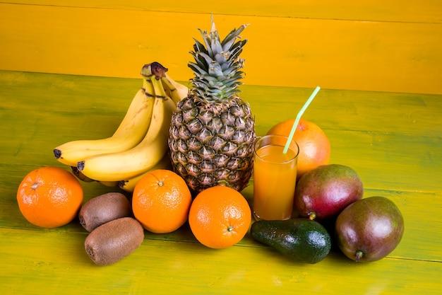 Owoce tropikalne na żółtym tle drewniane, świeża żywność.