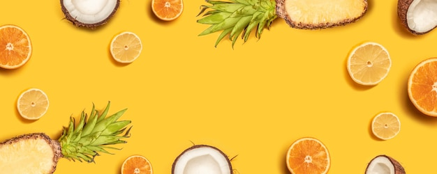 Owoce tropikalne płaskie leżał z ananasem, pomarańczami, cytryną i kokosem na pastelowym tle.