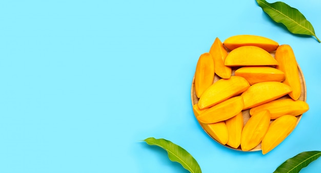 Owoce tropikalne, plastry mango na drewnianym talerzu na niebieskim tle. widok z góry