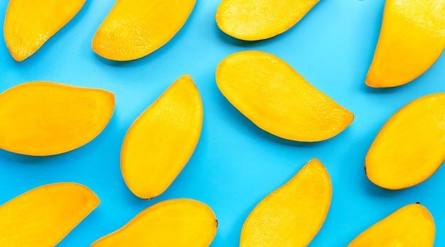 Owoce tropikalne, plastry mango na niebieskim tle. widok z góry