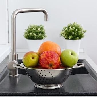 Owoce w filiżance na zlewie kuchennym w pobliżu kranu.