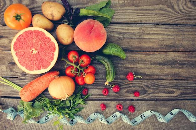 Owoce, warzywa iw miarce taśmy w diecie na drewnianym tle. stonowany obraz.