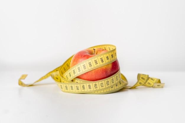 Owocowa i centymetrowa taśma na białej powierzchni. koncepcja diety