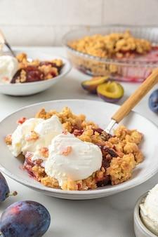 Owocowa kruszonka. ciasto z kruszonką śliwkową z lodami waniliowymi w talerzach z łyżkami na białym marmurowym stole na smaczne śniadanie. orientacja pionowa