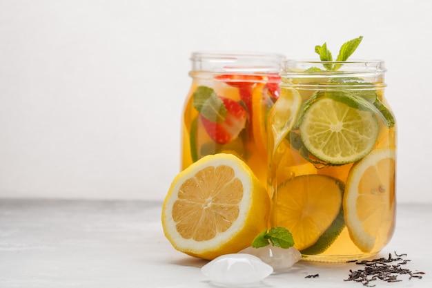 Owocowa lodowa herbata i imbirowa ziołowa lodowa herbata z mennicą w szklanych słojach, biały tło, kopii przestrzeń. lato orzeźwiający napój koncepcja.