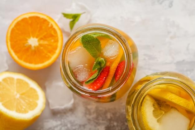 Owocowa lodowa herbata i imbirowa ziołowa lodowa herbata z mennicą w szklanych słojach, biały tło, odgórny widok, kopii przestrzeń. lato orzeźwiający napój koncepcja.