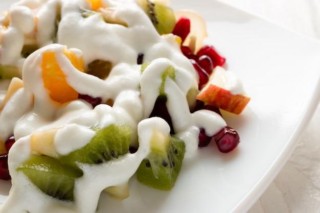 Owocowa sałatka mżąca z lody zbliżenia bielu talerzem