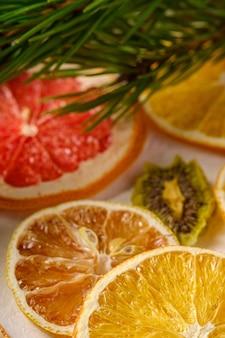 Owocowa tekstura z wysuszonym grejpfrutem, kiwi, pomarańcze i cytryną z gałąź jedlinowy drzewo, makro-