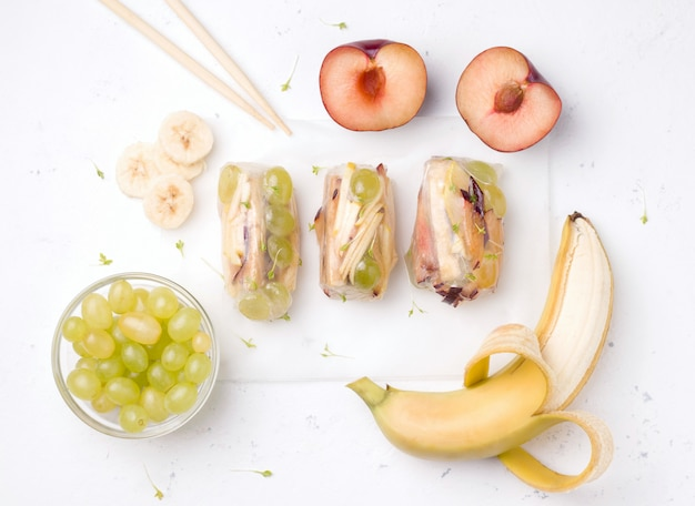 Owocowe rolki obok składników na bielu.