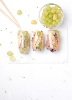 Owocowe słodkie sajgonki z jabłka, śliwki, winogron, bananów w papierze ryżowym, na białym betonie. dom z pałeczkami i składnikami.