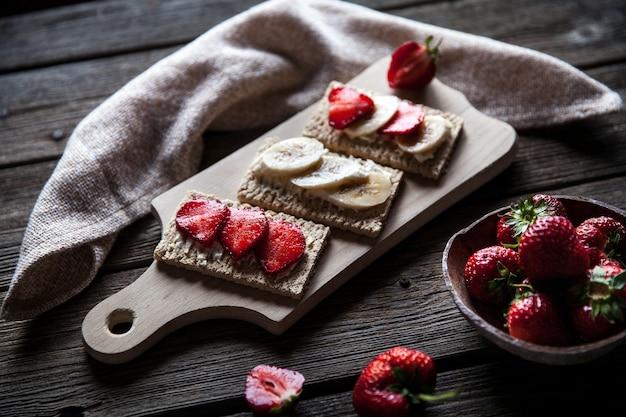 Owocowe tosty na drewnianym stole. truskawki, pieczywo, masło i ser. styl vintage i
