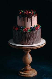 Owocowy czekoladowy tort na drewnianym stojaku na czerni