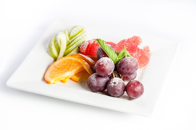 Owocowy deser na kwadratowym talerzu na białym tle