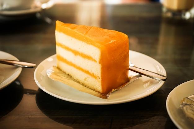 Owocowy pomarańczowy tort na białym talerzu dressert je z kawą relaksuje czas w restauraci