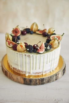 Owocowy tort urodzinowy z topperem, owocami na wierzchu i białą kroplą na beżowym tle