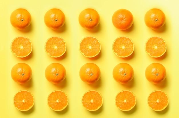 Owocowy wzór świezi pomarańczowi plasterki na żółtym tle. projekt pop-artu, koncepcja kreatywnego lata. połowa owoców cytrusowych w minimalistycznym stylu.