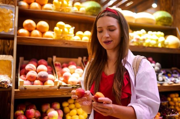 Owocując. urocza kobieta z pomarańczą w ręku stojąca w sklepie z owocami