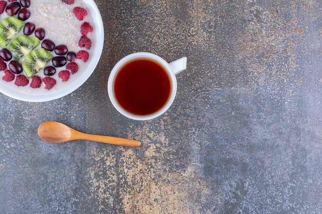 Owsianka mleczna z jagodami i filiżanką herbaty