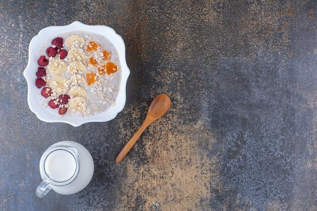 Owsianka mleczna z owocami, jagodami i filiżanką napoju