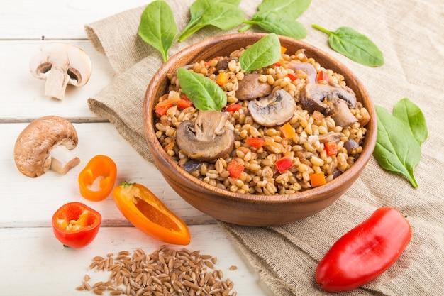 Owsianka orkiszowa (dinkel) z warzywami i grzybami w drewnianej misce na białym drewnianym stole i lnianej tkaniny. widok z boku, z bliska. rosyjska kuchnia tradycyjna.
