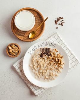 Owsianka owsiana na talerzu z napisem dzień dobry z czekoladą i orzechami oraz szklanką mleka. zdrowe jedzenie. śniadanie.