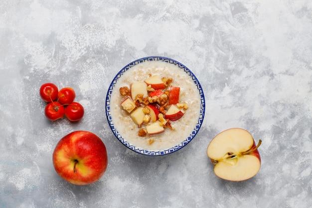 Owsianka owsiana w misce z miodem i plasterkami czerwonych jabłek, widok z góry
