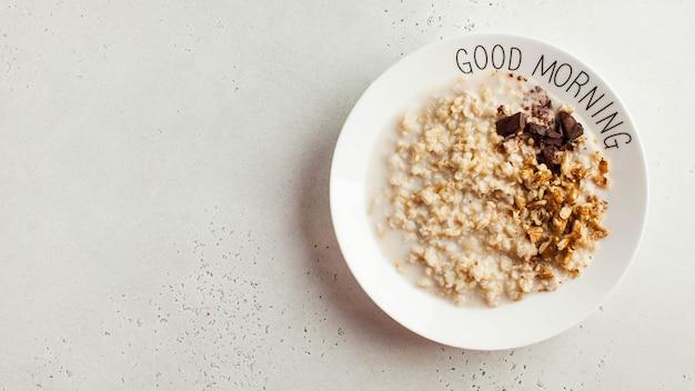 Owsianka owsiana z czekoladą i orzechami na talerzu z napisem dzień dobry. zdrowa żywność, śniadanie ...