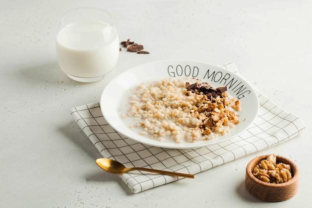 Owsianka owsiana z czekoladą i orzechami na talerzu z napisem dzień dobry. zdrowa żywność, wegetarianizm, śniadanie.