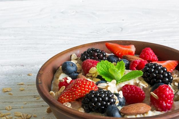 Owsianka owsiana z jagodami i orzechami w misce na zdrowe śniadanie