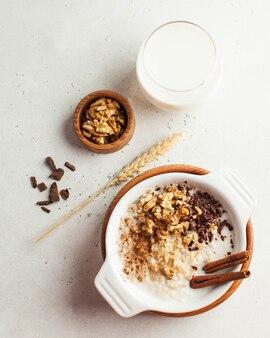 Owsianka owsiana z orzechami, cynamonem i czekoladą, szklanka mleka. śniadanie, zdrowa żywność .. dzień dobry.